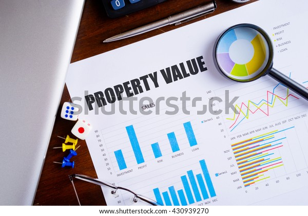 """""""Property Value"""" text on paper sheet with magnifying glass on chart, dice, spectacles, pen, laptop and blue and yellow push pin on wooden table - business, banking, finance and investment concept"""