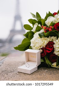 Proposal engagement ring with flowers under the Eiffel Tower in Paris, France.