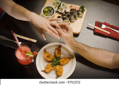 Proposal, Man giving ring to woman. Only hands and arms shown with sushi food at the table.