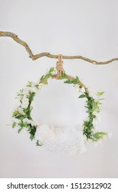 Props for shooting a newborn in a grape ring suspended on a branch decorated with floristry, cradle for a photo shoot with white flowers eustomas