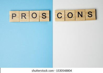"""Pros and Cons"" word in the wooden block on duo color background"