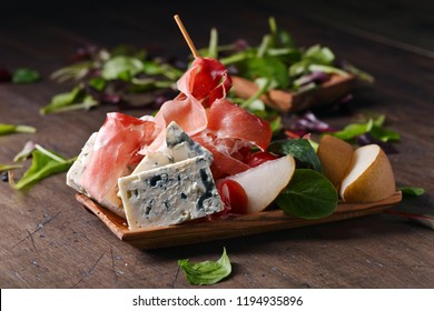 Prosciutto with blue cheese, pear and spinach on an old wooden table.