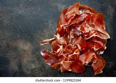 Prosciutto di parma or jamon serrano (iberico) on a dark slate, stone or metal background. Top view with copy space.