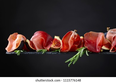 Prosciutto with figs and rosemary on a dark background.