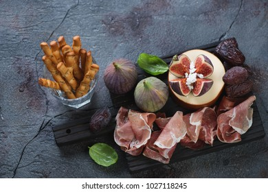 Prosciutto ham, cheese, figs, date fruits and salted breadsticks over cracked weathered asphalt background, horizontal shot