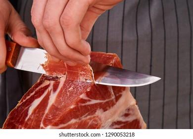 Prosciutto or jamon serrano. Close up on hands of a chef cutting traditional Italian Spanish ham. Slicing prepared hamon gastronomy background