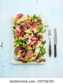 Prosciutto, melon, fig and soft cheese salad on a white serving board over grunge background, top view