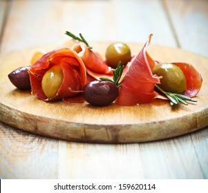 Prosciutto with olives and rosemary on the wooden background