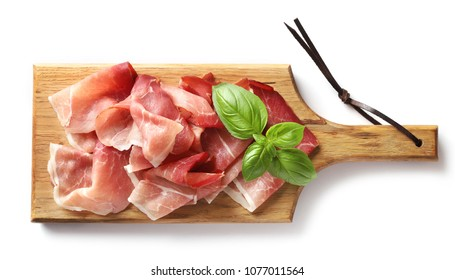 prosciutto on wooden cutting board isolated on white background, top view