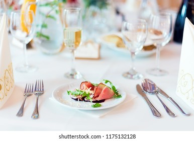 Prosciutto with parmesan cheese and rucola as a starter for wedding dish on the white table settings, light blurred background