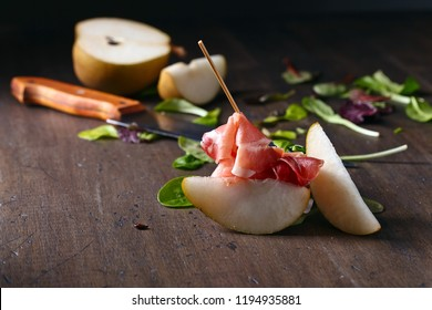 Prosciutto with pear and spinach on an old wooden table.