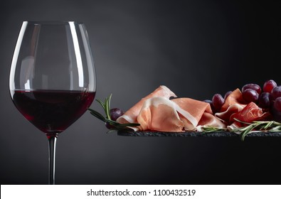 Prosciutto with rosemary and glass of red wine  on a old wooden table.