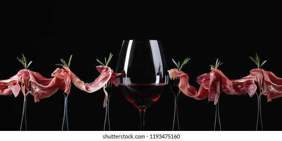 Prosciutto with rosemary and glass of red wine on a black background. Copy space for your text.