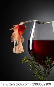 Prosciutto with  rosemary and glass of red wine on dark background. Copy space for your text.