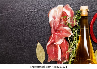 Prosciutto with rosemary and olive oil on stone table. Top view with copy space