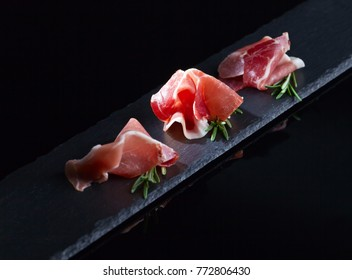 Prosciutto with rosemary on a black background.