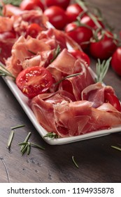 Prosciutto with  rosemary and tomatoes cherry on a old wooden table.