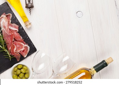 Prosciutto, wine, olives and olive oil on wooden table. Top view with copy space