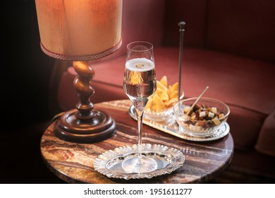Prosecco Valdobbiadene, an italian sparkling white whine; aperitif at home with snacks, dried fruit and seeds