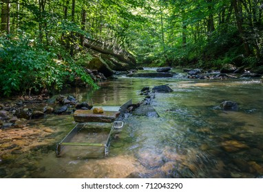 Prospecting and mining for gold and gemstones. Sluice box set in scenic rock riverbed.  Adventure and outdoor fun enjoying the fun recreation of gold panning.