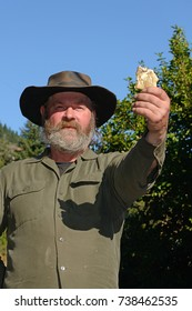 A prospector holds up a specimen of a gold nugget. Focus on prospector's face.