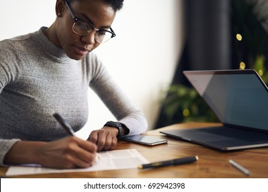 Prosperous afro american businesswoman writing report about company income analyzing information sitting near laptop computer, serious freelancer in eyewear planning working process and tasks