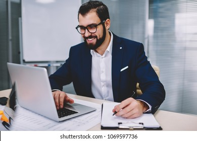 Prosperous bearded entrepreneur watching business webinar online on website on laptop computer connected to wireless 4G internet while writing down notes for productive work sitting in office