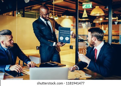 Prosperous executive manager holding graphic and charts communicating with crew of colleagues in meeting table, diversity group of male entrepreneurs analysing sponsorship idea using illustration data