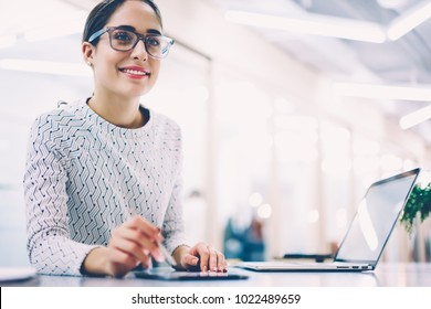Prosperous female administrative manager satisfied with occupation working at desktop with modern technologies,smiling woman in eyewear standing on reception in clinic organizing job waiting clients