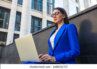 Prosperous female in glasses and suit searching information on website via laptop computer while sitting outdoors near business centre