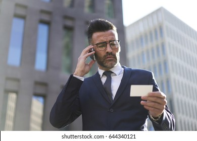 Prosperous mature business man having phone conversation with banking service using contact of call center from blanked visit card, professional male owner of company contact with partner via mobile