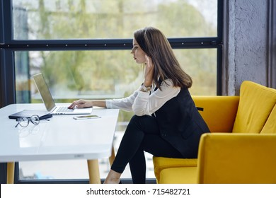 Prosperous owner of company dressed in formal outfit making remote job in cafe sitting on yellow couch, professional female economist concentrated on creating financial report using laptop computer