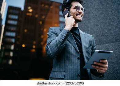 Prosperous young businessman received good news during mobile conversation on smartphone device while strolling on street with modern touch pad in hand.Successful economist talking on cellular