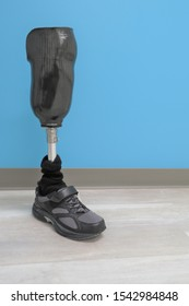 A prosthetic right leg with a metal pole and black shoe for an amputee with a below the knee amutation.  Copy space.