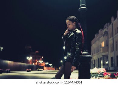 Prostitute with cigarette working on the night street. model informal appearance holding a cigarette in his hands. bad habit, harmful habit, pernicious habit, unhealthy habit