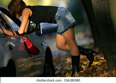 Prostitute in short skirt talking to a client sitting in a car.