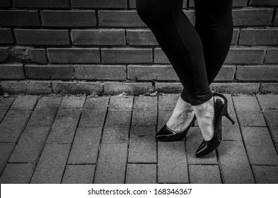 prostitution, prostitute standing against a wall on sidewalk with copy space