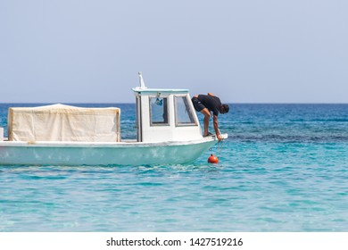 PROTARAS, CYPRUS - JUNE 3, 2019: Fisher doing his work on the boat. Blue water in the foreground
