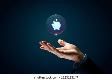 Protect investments and savings financial concept. Hand with soap bubble (symbol of dream) with symbol of the piggy bank inside.