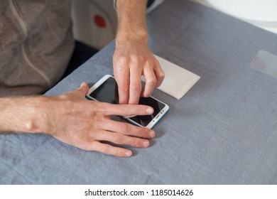 Protect, protective gadget concept. High angle top side profile view cropped photo guy hands wipe digital device screen with an alcohol cloth for glue a new protective glass at home