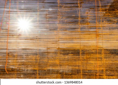Protect from sunlight in the room. Beige Bamboo Roll Background. Bamboo blinds Asian traditional home decoration. Sunlight coming through bamboo blinds by the window.