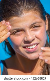Protect sunscreen applied to the face of smiling young girl