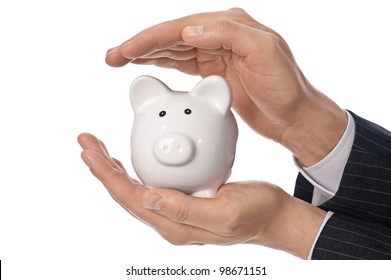 Protect your money concept. Two man's hands covering small white piggy bank isolated on white background.