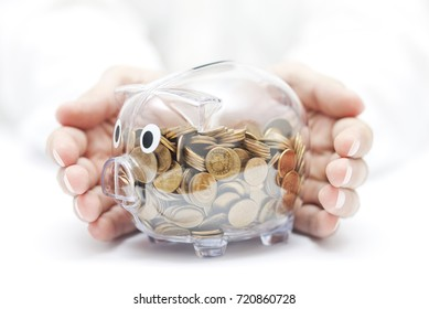 Protect your money. Transparent piggy bank with coins covered by hands.