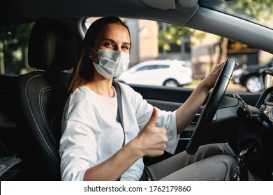 Protect yourself. Young woman with medical protective mask on her face is driving a car, she looks into camera and shows thumbs up. View from passenger seat