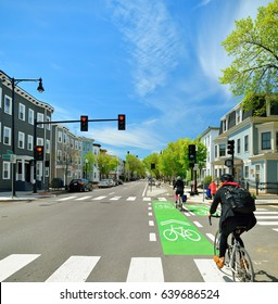 Protected bike lane between parking lane and sidewalk on city street. Bikers commuting on nice spring day.