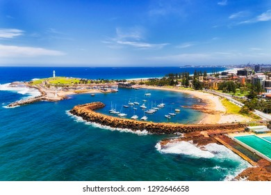 Protected Wollongong town harbour with marina and moored yachts behind sandstone breakwater wall and two white lighthouses with sandy beach on town coast.