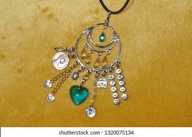 Protecting against evil. Luck amulet on textile background. Name amulet for good luck. Silver amulet with gems and pendants. Jewelry charm or talisman. Magic protecting the holder of amulet.