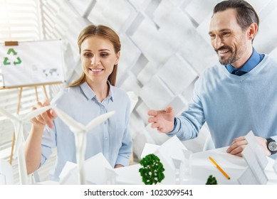 Protecting environment. Good-looking content fair-haired young woman smiling and working with her colleague on a project while sitting at the table