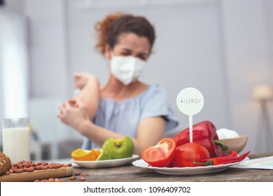 Protection from allergy. Young girl protecting her breathing passages with a respiratory mask so not to inhale a smell of vegetables causing her suffer from allergies